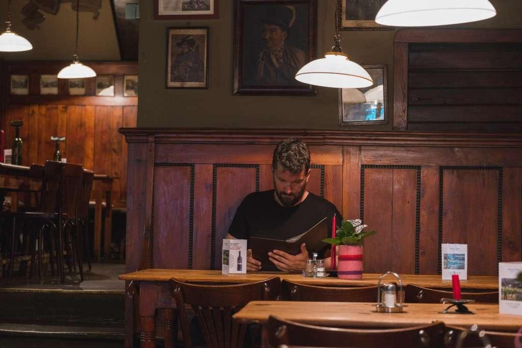Gerhard Reus at Andreas Hofer Weinstube reading the menu