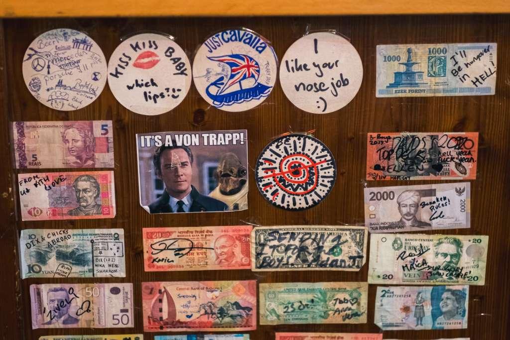 Scheine in verschiedenen Währungen an der Wand in der Bar des Yoho Hostels